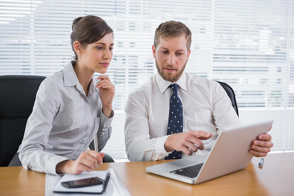 Business people working together on laptop in office at desk-2