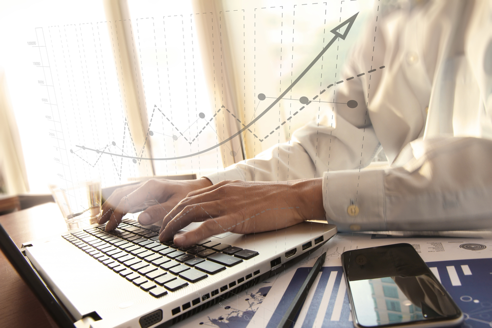 business man hand working on laptop computer on wooden desk as concept